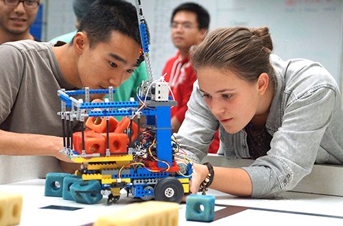 Image of two students collaborating on an mechanical project