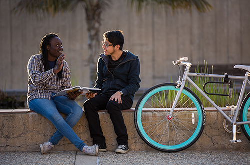 Image of two students discussing the textbook while sitting on a ledge, with bike perched against the edge