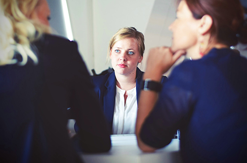 Image of a woman actively listening to others during a meeting